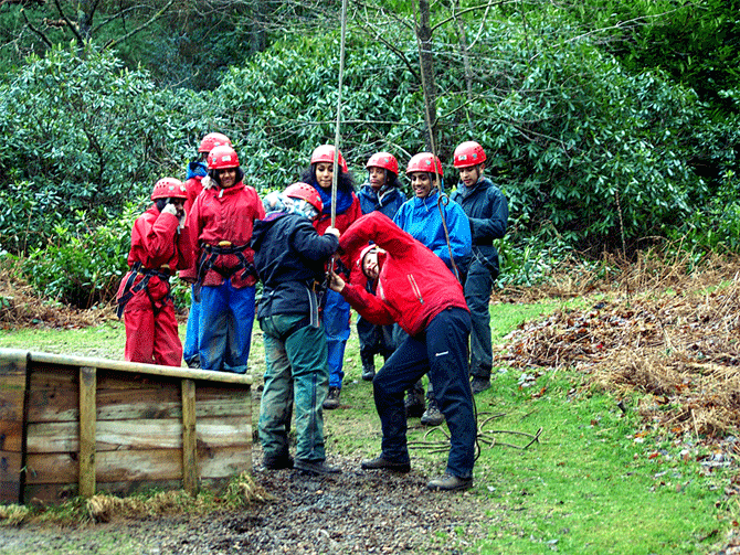 Students putting on safety gear before going on the zip line